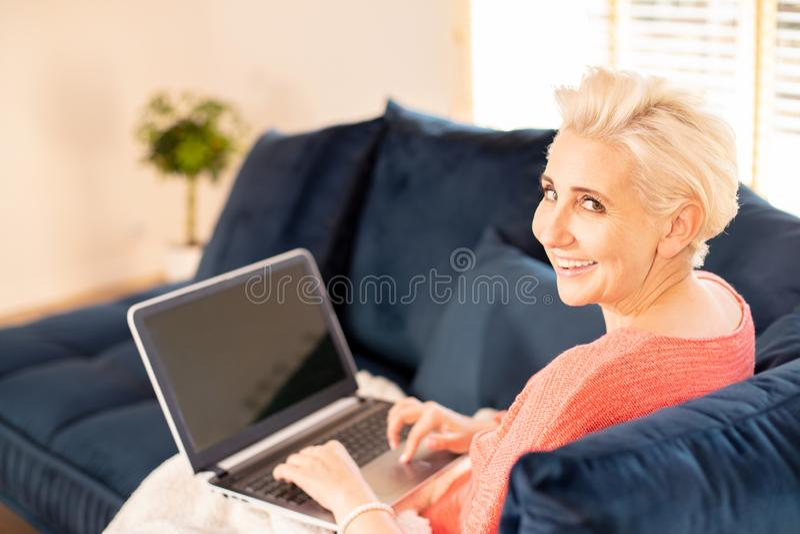 Ευτυχής ενήλικη γυναίκα που εργάζεται στο σπίτι στοκ εικόνα