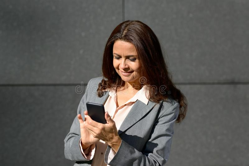 Ευτυχής ενήλικη γυναίκα που χρησιμοποιεί το smartphone στοκ φωτογραφία με δικαίωμα ελεύθερης χρήσης