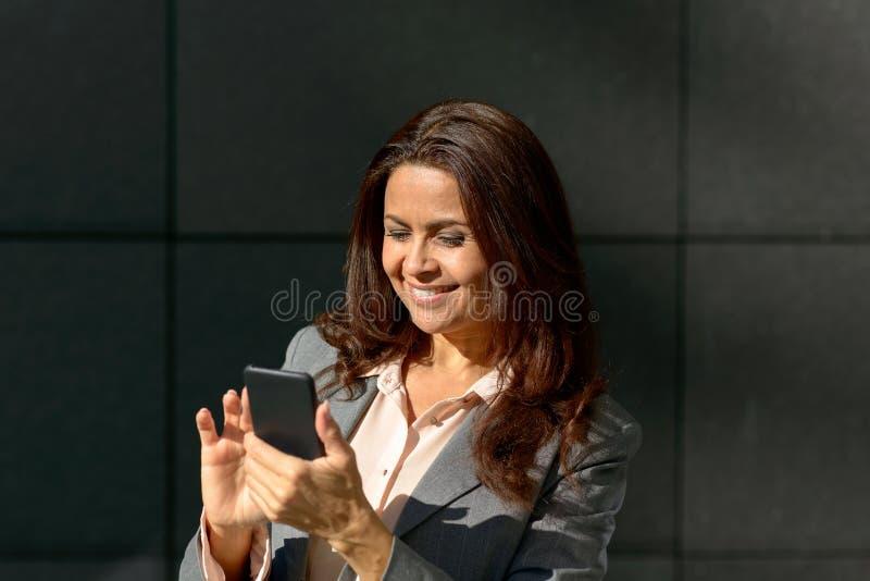 Ευτυχής ενήλικη γυναίκα που χρησιμοποιεί το smartphone στοκ φωτογραφίες