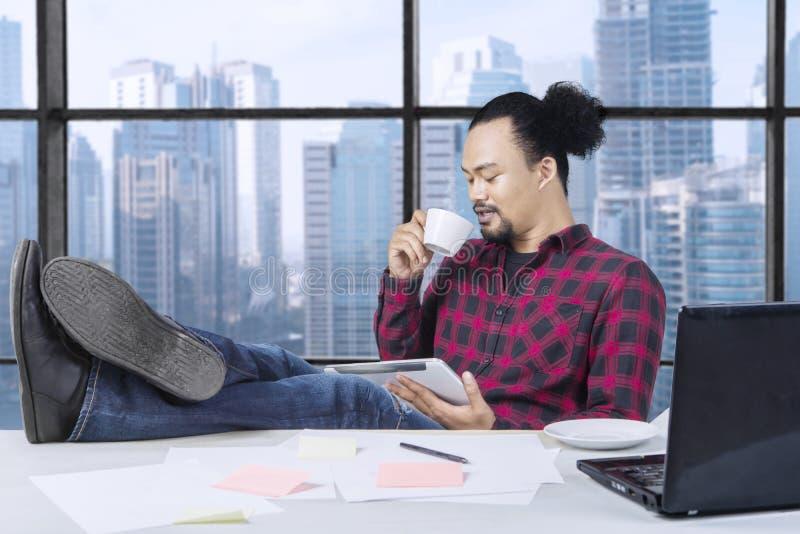 Ευτυχής επαγγελματικός εργαζόμενος που πίνει ένα φλιτζάνι του καφέ και τα πόδια στο γραφείο στοκ εικόνα