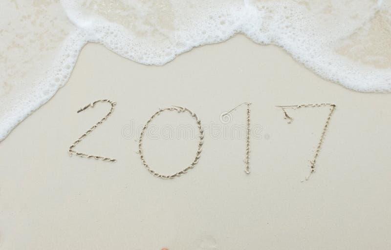 Ευτυχής επερχόμενη νέα έναρξη έτους 2017 με τη φρέσκια έννοια, αριθμοί 2017 χειρόγραφο στην άσπρη τροπική παραλία άμμου θάλασσας  στοκ εικόνες