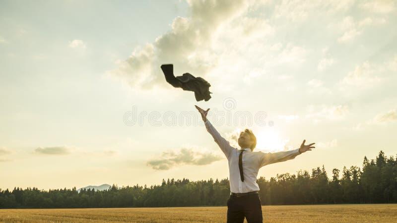 Ευτυχής επιτυχής επιχειρηματίας που ρίχνει το παλτό του στον αέρα στοκ εικόνες