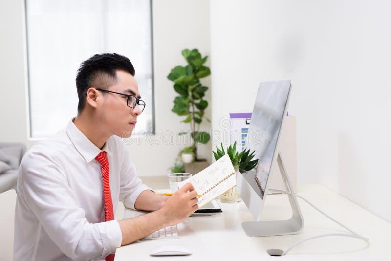 Ευτυχής επιχειρηματίας με τη διαθέσιμη εξέταση βιβλίων το όργανο ελέγχου υπολογιστών στοκ φωτογραφία με δικαίωμα ελεύθερης χρήσης