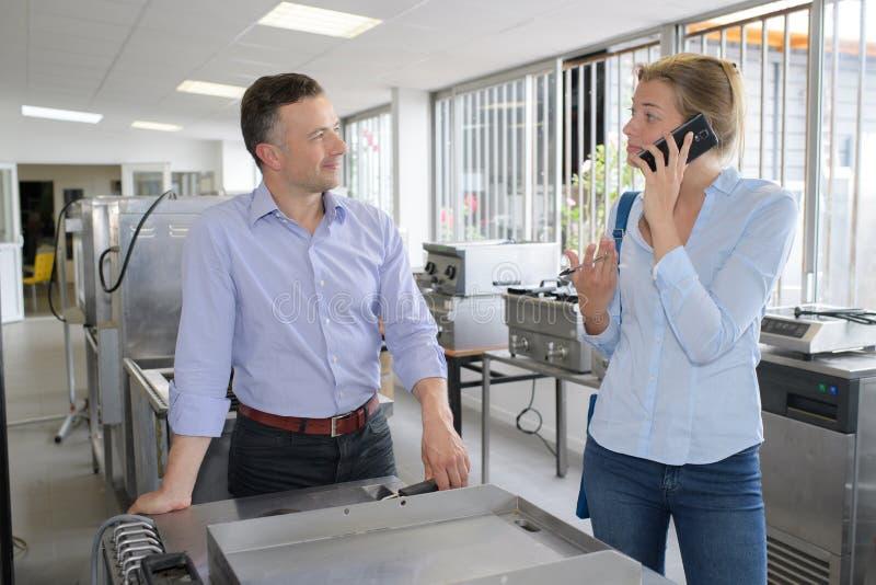 Ευτυχής επιχειρηματίας με τον άνδρα συνάδελφος στην αρχή στοκ εικόνες με δικαίωμα ελεύθερης χρήσης