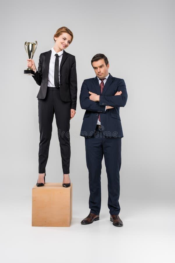 ευτυχής επιχειρηματίας με το φλυτζάνι τροπαίων που στέκεται στην εξέδρα, επιχειρηματίας που στέκεται πλησίον, στοκ εικόνες