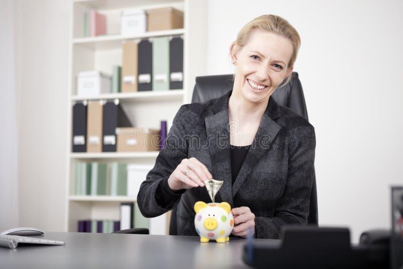 Ευτυχής επιχειρηματίας που βάζει τα χρήματα στην τράπεζα Piggy στοκ φωτογραφίες
