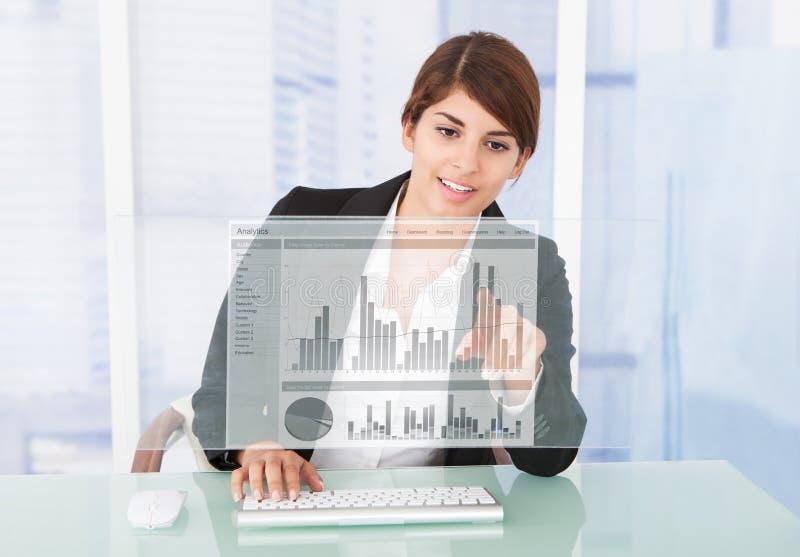 Ευτυχής επιχειρηματίας που εργάζεται στη γραφική παράσταση στο γραφείο υπολογιστών στοκ φωτογραφία με δικαίωμα ελεύθερης χρήσης