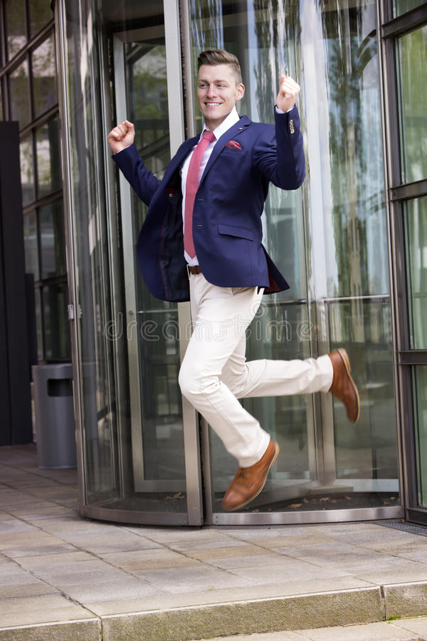 Ευτυχής επιχειρηματίας που πηδά μπροστά από το κτίριο γραφείων στοκ φωτογραφία