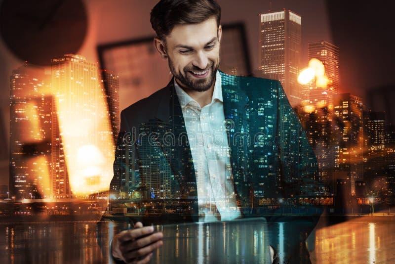 Ευτυχής επιχειρηματίας που προσέχει μια τηλεοπτική παρουσίαση για το lap-top στοκ φωτογραφία