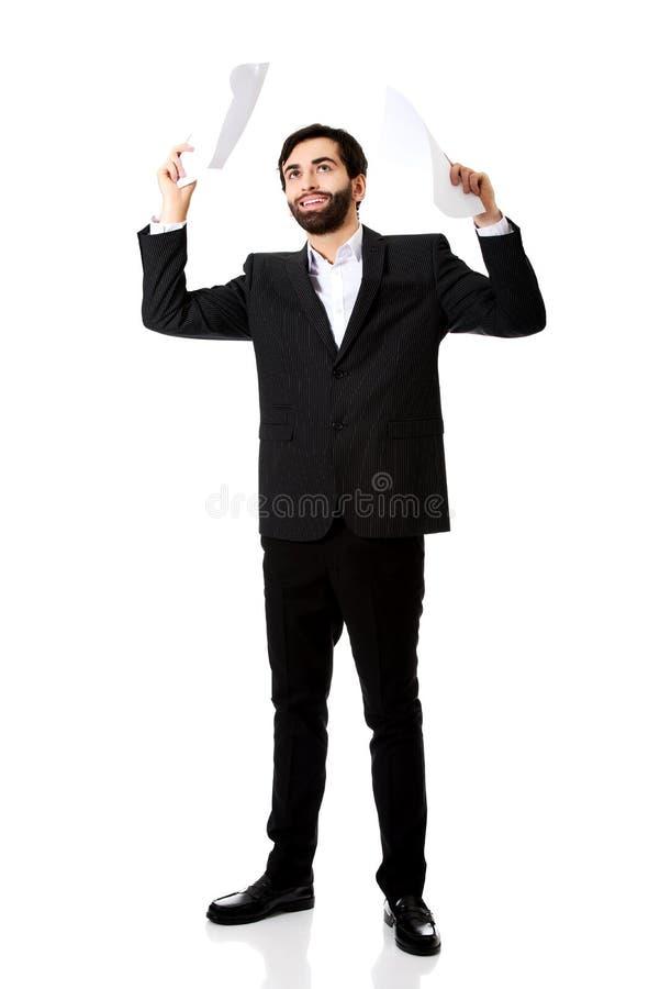 Ευτυχής επιχειρηματίας που ρίχνει τα φύλλα εγγράφου στοκ εικόνες