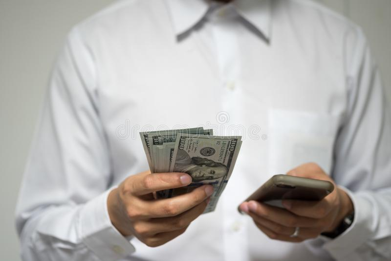 Ευτυχής επιχειρηματίας που χρησιμοποιεί τις κινητές πληρωμές και τις κινητές τραπεζικές εργασίες άτομο στοκ εικόνα με δικαίωμα ελεύθερης χρήσης