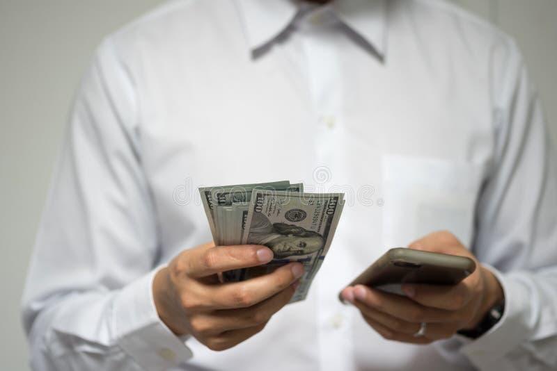 Ευτυχής επιχειρηματίας που χρησιμοποιεί τις κινητές πληρωμές και τις κινητές τραπεζικές εργασίες άτομο στοκ εικόνες
