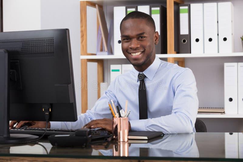 Ευτυχής επιχειρηματίας που χρησιμοποιεί τον υπολογιστή στοκ εικόνες