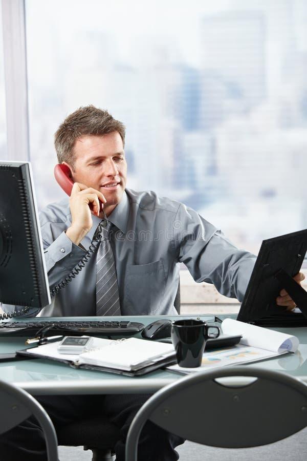 Ευτυχής επιχειρηματίας στο τηλέφωνο που καλεί την οικογένεια στοκ εικόνες