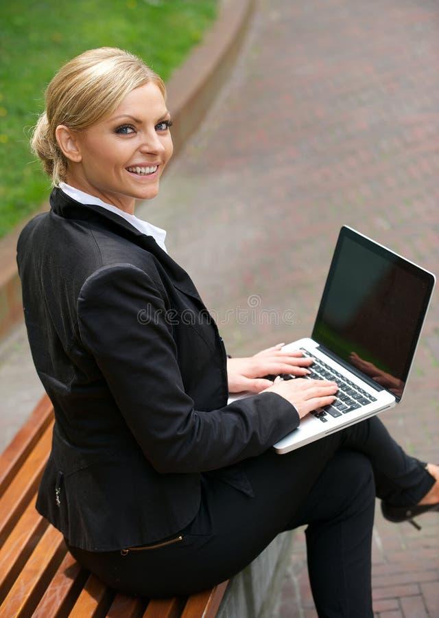 Ευτυχής επιχειρησιακή γυναίκα που εργάζεται στο lap-top στην πόλη στοκ φωτογραφία με δικαίωμα ελεύθερης χρήσης
