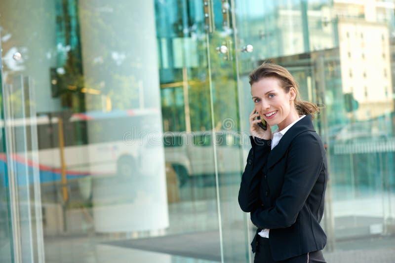 Ευτυχής επιχειρησιακή γυναίκα που περπατά και που καλεί με κινητό τηλέφωνο στοκ εικόνα