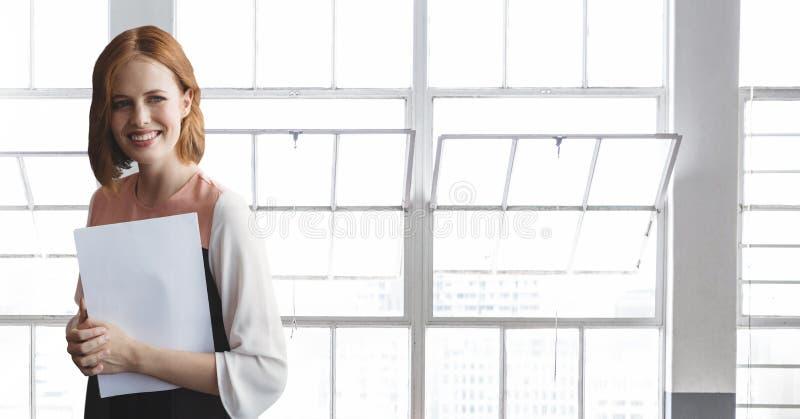 Ευτυχής επιχειρησιακή γυναίκα που στέκεται ενάντια στην οικοδόμηση του υποβάθρου στοκ εικόνες