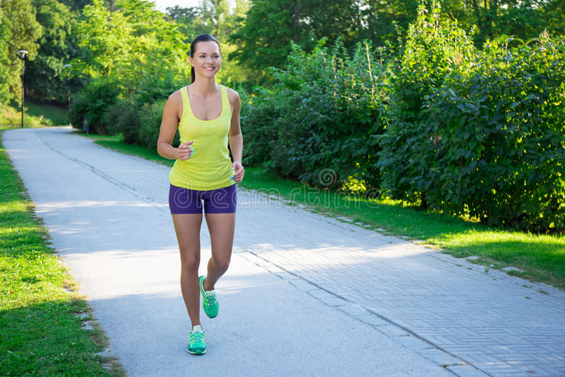 Ευτυχής λεπτή jogging γυναίκα που τρέχει στο πάρκο στοκ φωτογραφίες