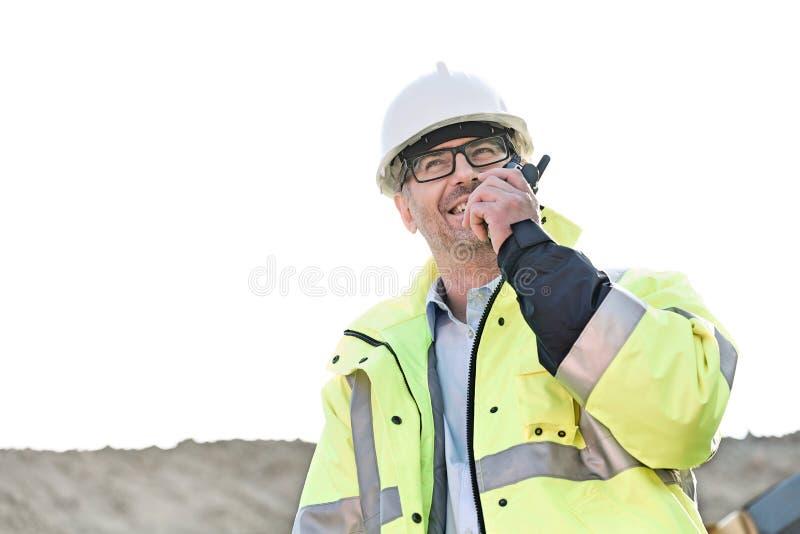 Ευτυχής επόπτης που χρησιμοποιεί walkie-talkie στο εργοτάξιο οικοδομής ενάντια στο σαφή ουρανό στοκ εικόνες με δικαίωμα ελεύθερης χρήσης