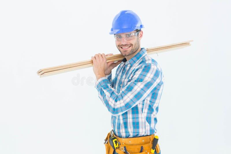 Ευτυχής εργάτης οικοδομών που φέρνει τις ξύλινες σανίδες στοκ φωτογραφίες