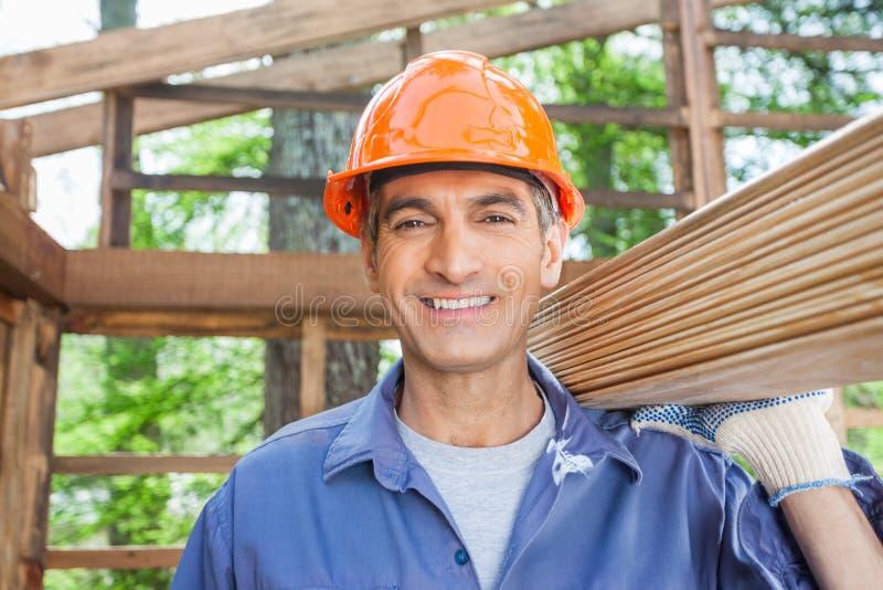 Ευτυχής εργάτης οικοδομών που φέρνει τις ξύλινες σανίδες στοκ εικόνες