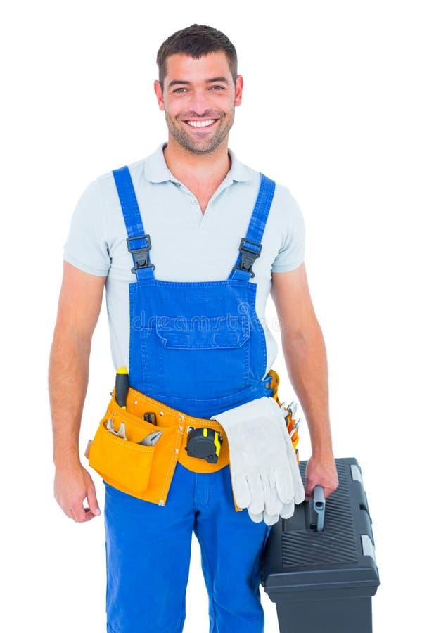 Ευτυχής εργάτης στις φόρμες που κρατά την εργαλειοθήκη στοκ εικόνα με δικαίωμα ελεύθερης χρήσης