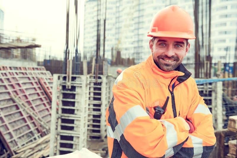 Ευτυχής εργαζόμενος οικοδόμων στο εργοτάξιο οικοδομής στοκ φωτογραφία