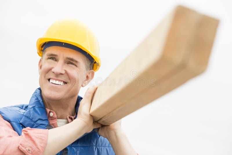 Ευτυχής εργαζόμενος που φέρνει την ξύλινη σανίδα ενάντια στο σαφή ουρανό στοκ φωτογραφία με δικαίωμα ελεύθερης χρήσης