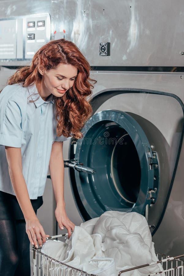 ευτυχής εργαζόμενος στεγνού καθαρισμού θηλυκών που παίρνει τα ενδύματα από στοκ φωτογραφίες