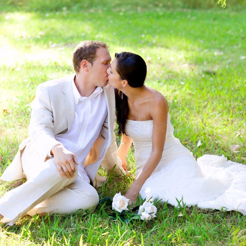 Ευτυχής ερωτευμένη συνεδρίαση φιλήματος ζεύγους στο πάρκο στοκ εικόνα με δικαίωμα ελεύθερης χρήσης