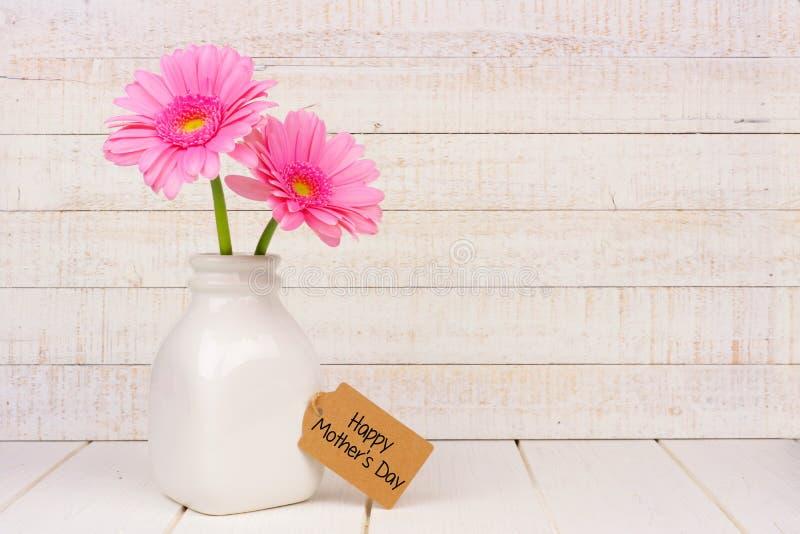 Ευτυχής ετικέττα ημέρας μητέρων με τα ρόδινα λουλούδια ενάντια στο άσπρο ξύλο στοκ φωτογραφίες με δικαίωμα ελεύθερης χρήσης