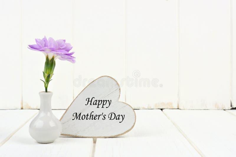 Ευτυχής ετικέττα καρδιών ημέρας μητέρων με το γαρίφαλο ενάντια στο άσπρο ξύλο στοκ φωτογραφία