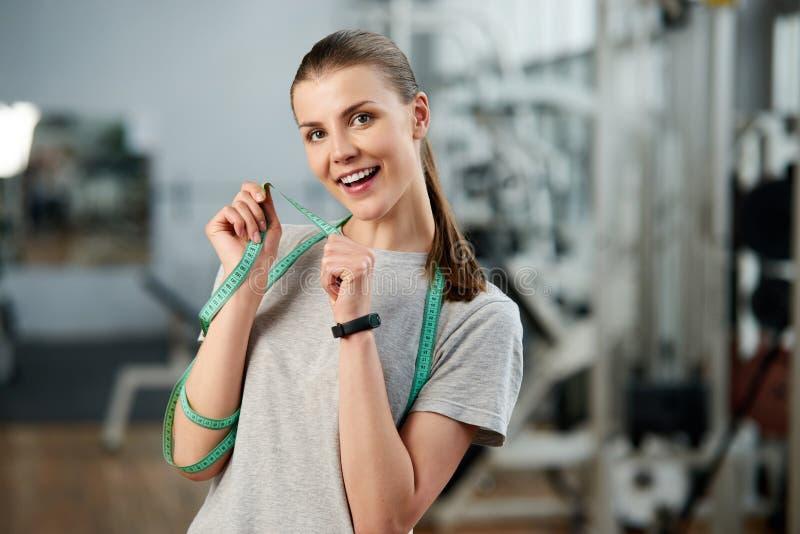 Ευτυχής ευχαριστημένη γυναίκα με τη μέτρηση της ταινίας στη γυμναστική στοκ φωτογραφίες
