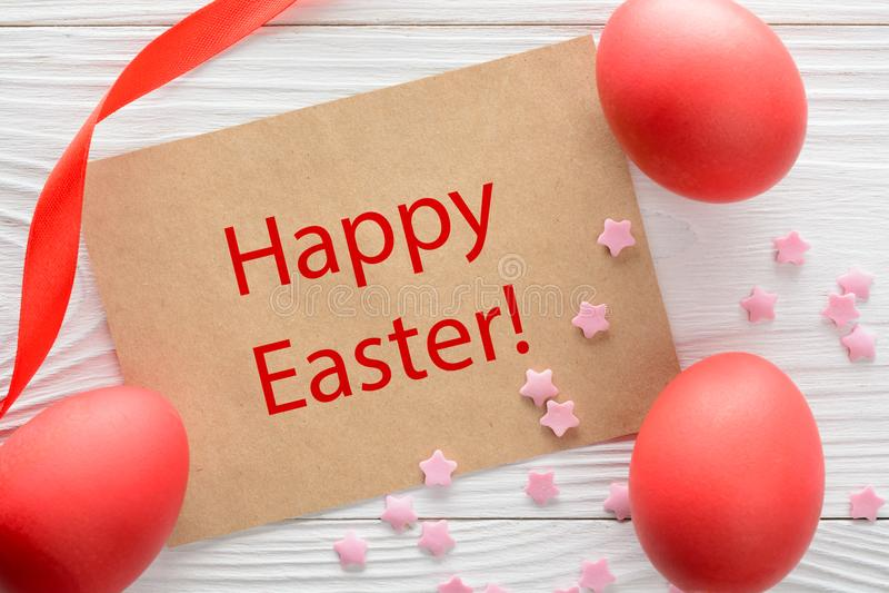 Ευτυχής ευχετήρια κάρτα Πάσχας και ζωηρόχρωμα αυγά στον ξύλινο πίνακα Τοπ όψη στοκ φωτογραφία