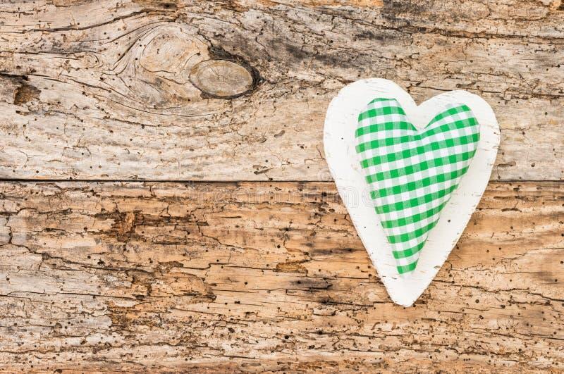 Ευτυχής ευχετήρια κάρτα Πάσχας με την πράσινη ελεγχμένη καρδιά στο αγροτικό ξύλο στοκ φωτογραφίες