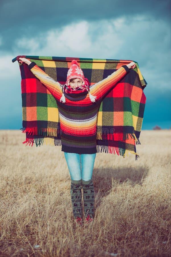 Ευτυχής ελεύθερη γυναίκα ξένοιαστη το φθινόπωρο ή το χειμώνα κάτω από ένα θερμό κάλυμμα που απολαμβάνει τον ήλιο στοκ φωτογραφία