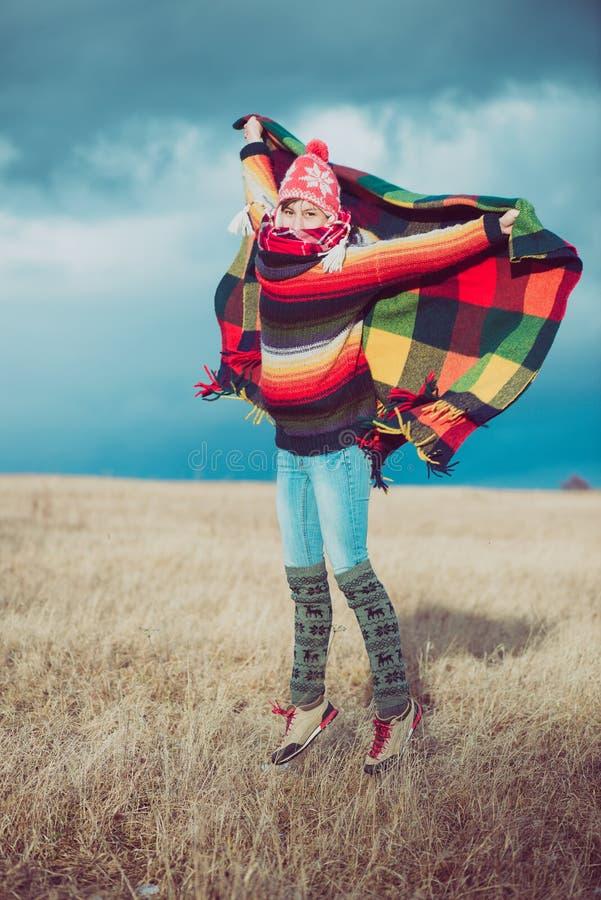 Ευτυχής ελεύθερη γυναίκα ξένοιαστη το φθινόπωρο ή το χειμώνα κάτω από ένα θερμό κάλυμμα που απολαμβάνει τον ήλιο στοκ εικόνες με δικαίωμα ελεύθερης χρήσης