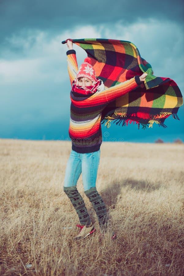 Ευτυχής ελεύθερη γυναίκα ξένοιαστη το φθινόπωρο ή το χειμώνα κάτω από ένα θερμό κάλυμμα που απολαμβάνει τον ήλιο στοκ εικόνα