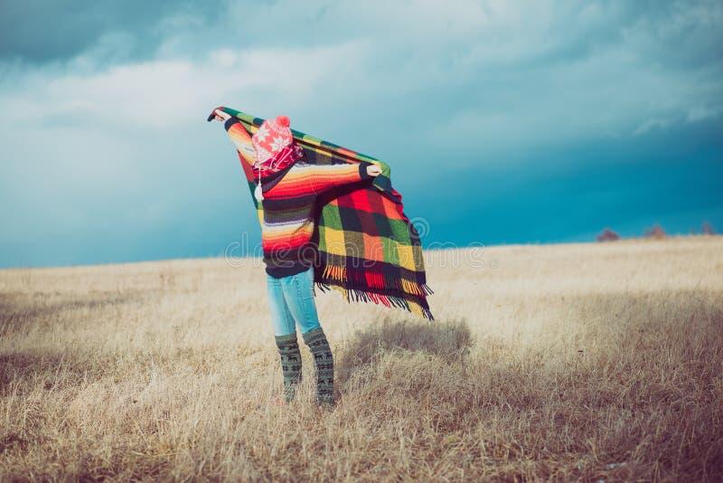 Ευτυχής ελεύθερη γυναίκα ξένοιαστη το φθινόπωρο ή το χειμώνα κάτω από ένα θερμό κάλυμμα που απολαμβάνει τον ήλιο στοκ εικόνες