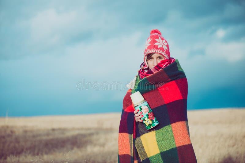 Ευτυχής ελεύθερη γυναίκα ξένοιαστη το φθινόπωρο ή το χειμώνα κάτω από ένα θερμό κάλυμμα που απολαμβάνει τον ήλιο στοκ φωτογραφία με δικαίωμα ελεύθερης χρήσης