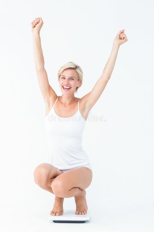 Ευτυχής ελκυστική γυναίκα που σκύβει τις κλίμακες στοκ εικόνα με δικαίωμα ελεύθερης χρήσης