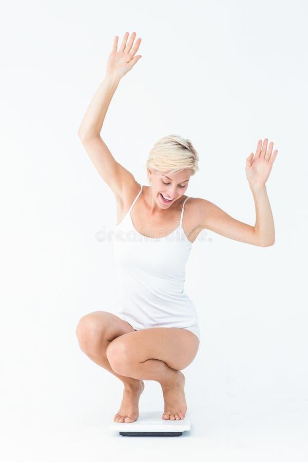 Ευτυχής ελκυστική γυναίκα που σκύβει τις κλίμακες στοκ φωτογραφία