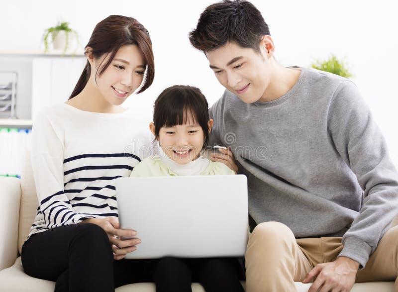 Ευτυχής ελκυστική νέα οικογένεια που προσέχει το lap-top στοκ φωτογραφίες με δικαίωμα ελεύθερης χρήσης