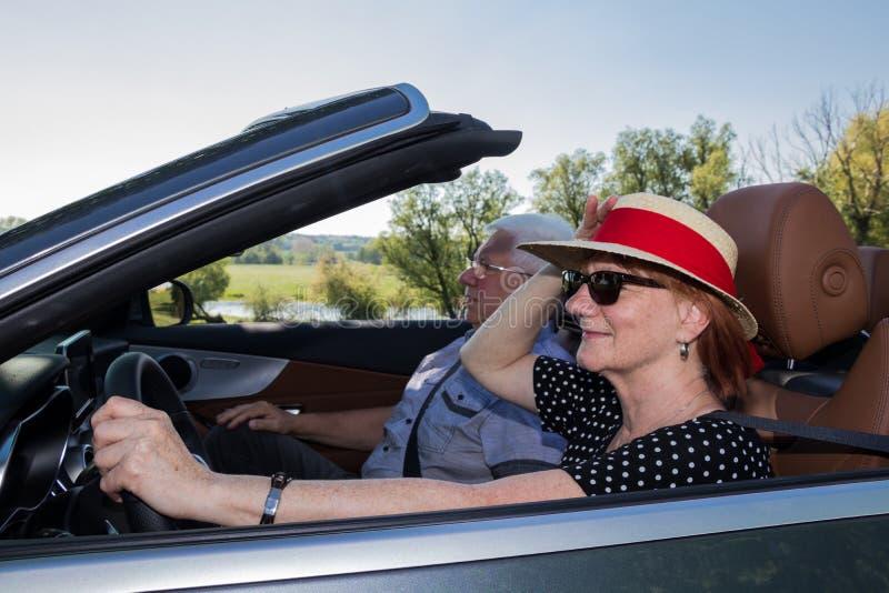 Ευτυχής ηλικιωμένη γυναίκα με ένα καπέλο ήλιων και ο συνεργάτης της σε ένα μετατρέψιμο αυτοκίνητο πολυτέλειας στοκ φωτογραφίες