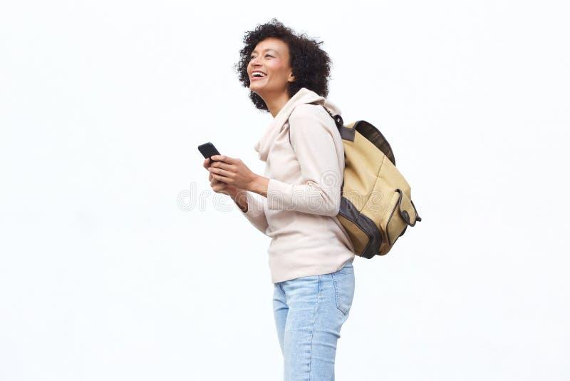 Ευτυχής ηλικιωμένη γυναίκα με την τσάντα και κινητό τηλέφωνο στο απομονωμένο άσπρο κλίμα στοκ εικόνα