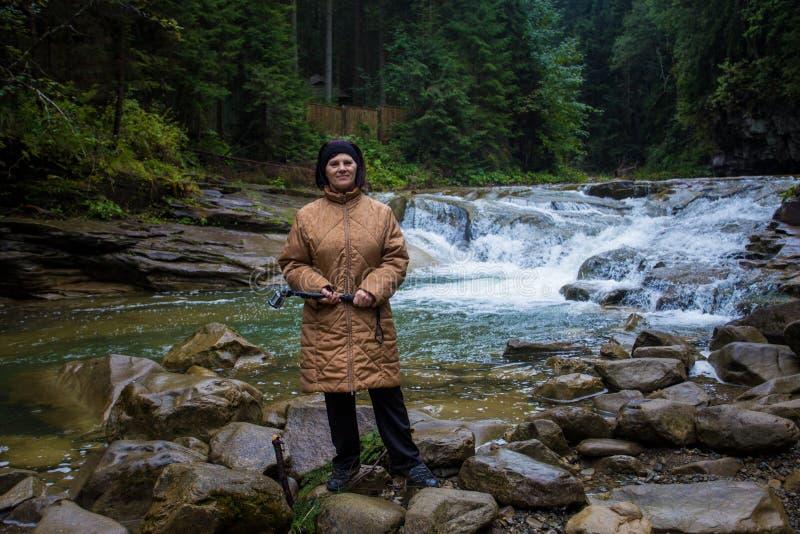 Ευτυχής ηλικιωμένη γυναίκα που στέκεται κοντά σε ένα ρεύμα βουνών στοκ εικόνα με δικαίωμα ελεύθερης χρήσης