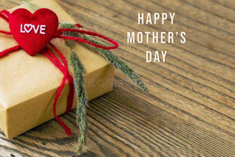 Ευτυχής ημέρα μητέρων, μορφή καρδιών με τη λέξη ΑΓΑΠΗΣ, κιβώτιο δώρων και λουλούδι στοκ εικόνες