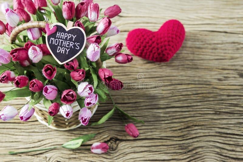 Ευτυχής ημέρα μητέρων των ρόδινων και κόκκινων λουλουδιών τουλιπών στο ξύλινο καλάθι στοκ εικόνες