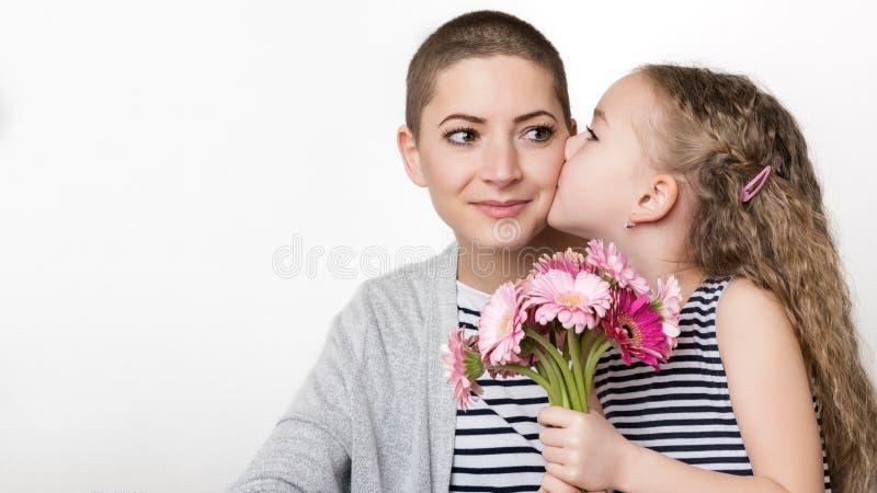 Ευτυχής ημέρα μητέρων ` s, ημέρα γυναικών ` s ή υπόβαθρο γενεθλίων Χαριτωμένο μικρό κορίτσι που δίνει mom, επιζών καρκίνου, ανθοδ στοκ φωτογραφία