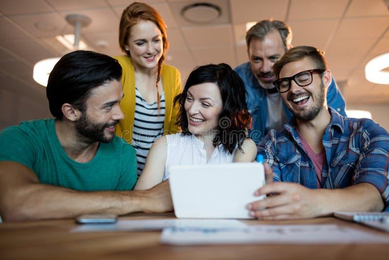 Ευτυχής δημιουργική επιχειρησιακή ομάδα που συζητά πέρα από την ψηφιακή ταμπλέτα στοκ εικόνες